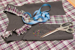 Top view of child billet school dress lying on the table with sewing accessories Royalty Free Stock Photography