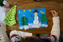 Top view of child, doing snowman and winter tree. Scissors, glue royalty free stock images