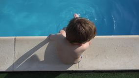 Top view of child on the edge of the pool, playing with feet in the blue water, enjoy summer holiday. UHD 4K stock video