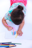 Top view. Child lie on the floor and drawing on paper.  On white Royalty Free Stock Photo