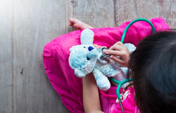 Top view of child playing doctor or nurse with plush toy bear at Stock Photo