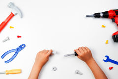 Top view on child`s hands with colorful toys tools on the white background. Top view on child`s hands playing with colorful toys tools on the white background Stock Photography