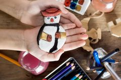 Top view child`s hands holding vintage christmas toys. Paints and brushes on table in background. Kids activity concept. New year Stock Photo