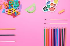 Top view of the child`s table, the composition of the paint brush letters numbers color pencils eraser different line on a pink royalty free stock image