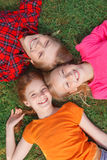Top view of children lying on the grass Stock Photos