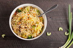 Top view of chinese chicken lo mein on dark wooden background. Chinese chicken lo mein with cabbage, carrots, celery, mushrooms, turnips, broccoli, and assorted stock photography