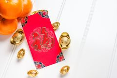 Top view Chinese New year red envelope packet ang pow with g. Old ingots and tangerine on white wood table top,Chinese Language on envelop mean Happiness and on royalty free stock image