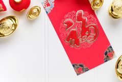 Top view Chinese New year red envelope packet ang pow with gol. D ingots on white wood table top,Chinese Language on envelop mean Happiness and on ingot mean ` royalty free stock photo
