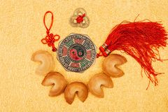 Chinese talisman surrounded with fortune cookies on golden surface, Chinese New Year concept. Top view of chinese talisman surrounded with fortune cookies on Stock Photo