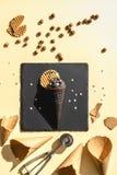 Top view of chocolate black ice cream and empty ice cream cones. On yellow stock image