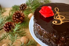 Top View Of A Chocolate Cake With A Stylized Image Of A Musical Staff Stave With A G-Clef And A Red Rose On A Wooden Background royalty free stock photography