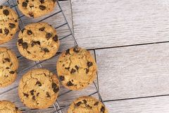 Top view of chocolate chip cookies on a cooling rack, white wooden plank in background. Copy space for your text royalty free stock images