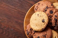 Top view of chocolate chip cookies on a wooden plate over rustic background, selective focus. Top view of chocolate chip cookies on a wooden plate over rustic Royalty Free Stock Photo