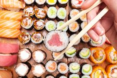 Top view of chopsticks with roll over lot of sushi. Top view of chopsticks with tuna nori roll over lot of sushi and rolls on wooden table royalty free stock photography