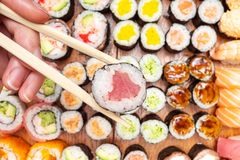 Top view of chopsticks with roll over many sushi. Top view of chopsticks with tuna nori roll over many sushi and rolls on wooden table royalty free stock photography