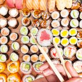 Top view of chopsticks with roll over set of sushi. Top view of chopsticks with tuna nori roll over set of sushi and rolls on wooden table royalty free stock photos