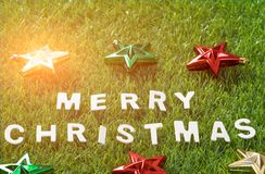 Top view Christmas alphabet and decoration on green grass Royalty Free Stock Image