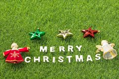 Top view Christmas alphabet and decoration on green grass. Background, Celebration of New year and Christmas Royalty Free Stock Images