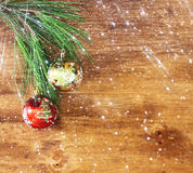 Top view Christmas background with ornament, gift box, and fir over wooden table with bokeh lights Stock Images
