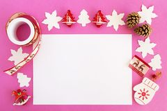 Top view on the Christmas decorations, pine cones and white sheet of paper on the pink background. Royalty Free Stock Photos
