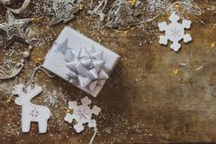 Top view of Christmas decorations, silver wrapped Christmas gift and decorations on a wooden background royalty free stock images
