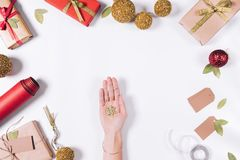 Top view of Christmas decorations on a white table. And female hands with a decorative snowflake on a palm Stock Images