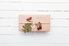 Top view of christmas gift wrapped in craft and decorated with various natural things on white wood Stock Photos