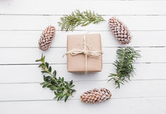 Top view of christmas gift wrapped in craft and decorated with various natural things on white wood Royalty Free Stock Images