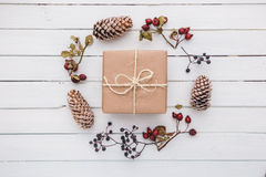 Top view of christmas gift wrapped in craft and decorated with various natural things on white wood. Top view on christmas gift wrapped in craft and decorated Stock Image