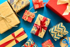 Top view on Christmas gifts wrapped in gift paper decorated with ribbon on blue paper background. New Year, holidays and celebration decorations concept. Copy Stock Images