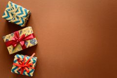 Top view on Christmas gifts wrapped in gift paper decorated with ribbon on brown paper background. stock photos