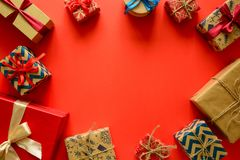 Top view on Christmas gifts wrapped in gift paper decorated with ribbon on red paper background. stock image