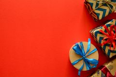 Top view on Christmas gifts wrapped in gift paper decorated with ribbon on red paper background. New Year, holidays and celebration decorations concept. Copy Stock Photos