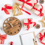 Top view Christmas holidays composition with gifts in craft paper with red satin ribbon, decor, watch and notebook on the white wo Stock Images