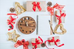 Top view Christmas holidays composition with gifts in craft paper with red satin ribbon, decor, watch and notebook on the white wo Stock Photo