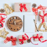 Top view Christmas holidays composition with gifts in craft paper with red satin ribbon, decor, watch and notebook on the white wo Royalty Free Stock Photos