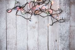 Top view of Christmas lights on wooden table background. Free space for text. Seasonal, Festival and Holiday Concept Royalty Free Stock Images