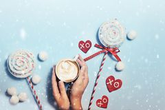 Snowy greeting card. Top view Christmas mood, snow toned, hands holding a cup of cappuccino, candies and cookies Stock Photos