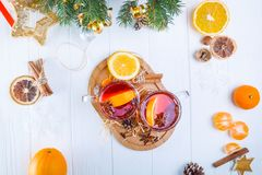 Top view Christmas mulled wine, Hot winter drink with berries, orange,spices, cinnamon in glass cups on the white wooden table wit Stock Photo