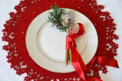 Christmas Table Place Setting with cutlery, branch of Christmas tree and red ribbon on red woolen and white background. New Year stock images