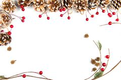 Christmas ornaments white background. A top view of a Christmas ornaments background: with a frame of pine cones with red berries and a branch curved at the stock photos