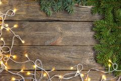 Christmas close-up of Christmas tree branches and Chistmas lights on vintage wooden background. Top view of a Christmas workplace. New Year frame or Xmas Mockup Stock Images