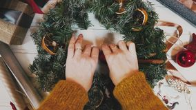 Top view Christmas wreath on craft background, pretty famale hand decorate christmas wreath, motion shot.  stock video