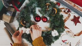 Top view Christmas wreath on craft background, pretty famale hand decorate christmas wreath, motion shot.  stock video footage