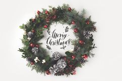 Christmas wreath with balls and pine cones. Top view of christmas wreath made with Merry christmas lettering, isolated on white royalty free stock photo