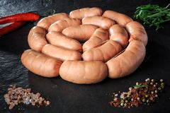 Top view on circle of raw short sausages with rucola and chili. Top view on circle set of raw short thick sausages served with pink salt, spices, rucola and stock photos