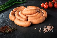 Top view circle of short sausages with onion and tomatoes. Top view on circle of short thick meat sausages served with pink salt, spices, green onion and stock photography