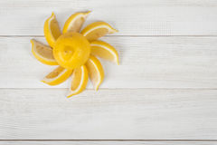 Top view of citrus slices laid out into the sun shape around whole lemon on wooden surface. Royalty Free Stock Photos
