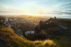 Top view on the city of Edinburgh and sitting man. Top view from the mountains of Edinburgh and a seated tourist looking out over the city at sunset. From Arthur stock photography