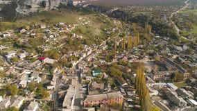 Top view of city in foothills of hills. Shot. Houses, roads and streets located on slopes of hills. Colourful old town. Is located in secluded area surrounded stock video footage